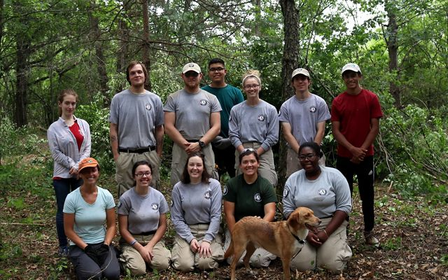 A group of AmeriCorps NCCC members and high school interns pose for the camera in the woods in the Mukwonago River Watershed