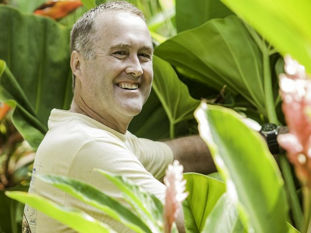 A smiling man standing in the jungle.
