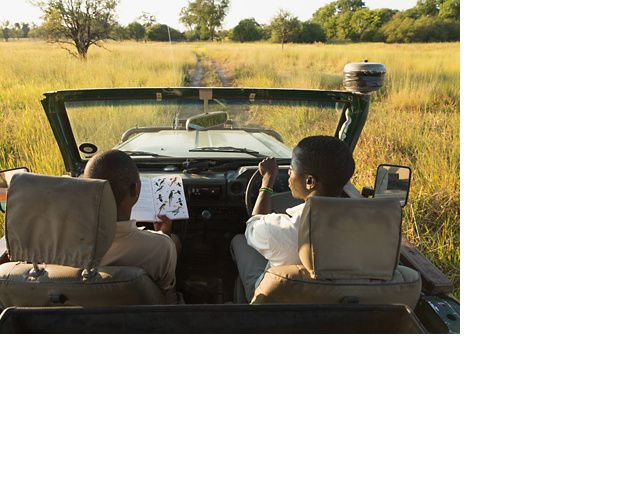 Two safari guides sit in an open-top truck and look at a bird identification book