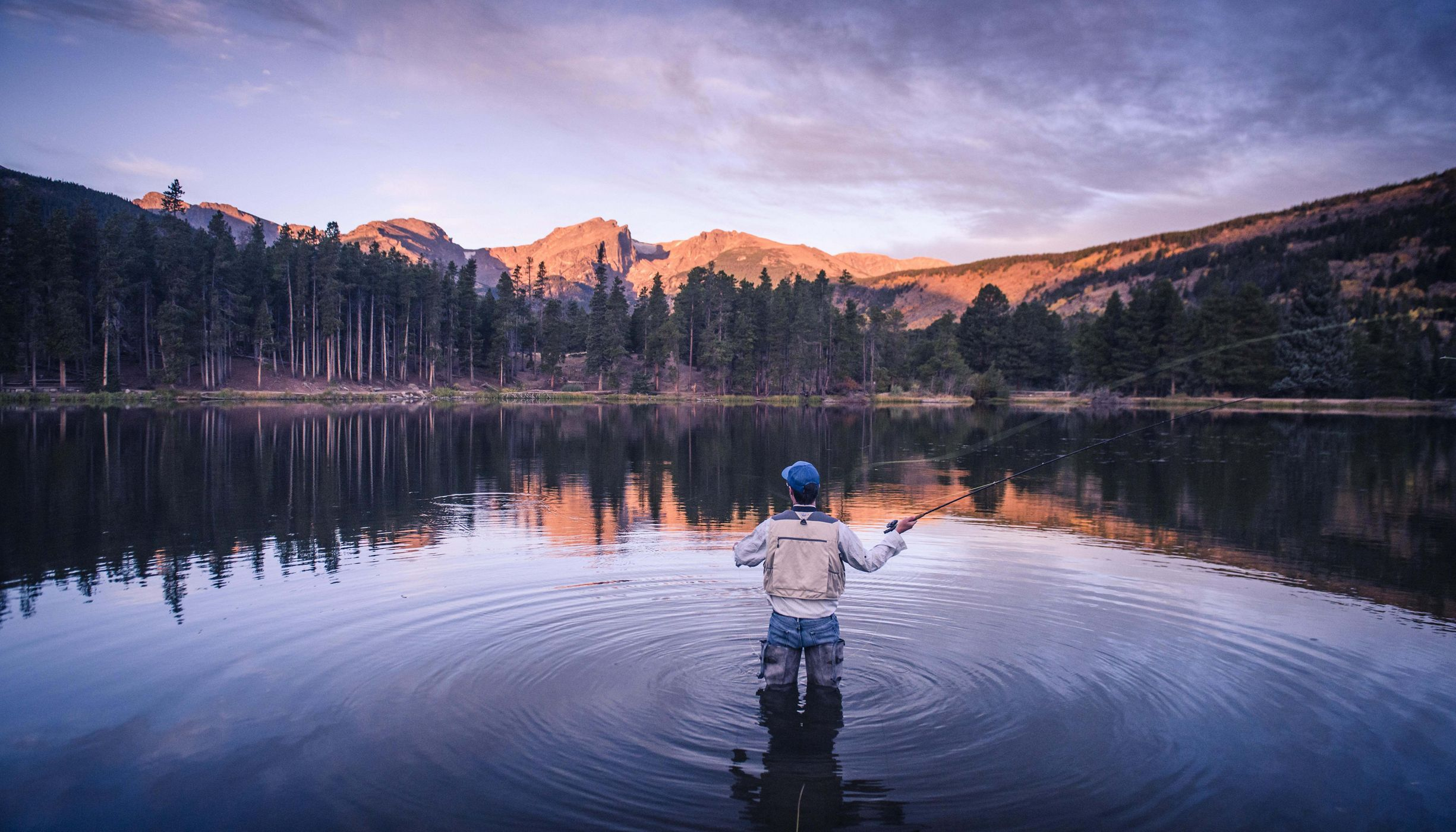 Photo of a man flyfishing in a pond in Rocky Mountain National Park, mountains in background.