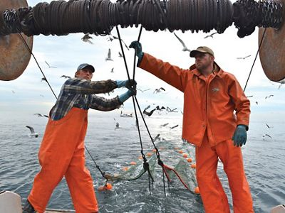Two fishermen in bright orange jackets pull rigging on a fishing boat.