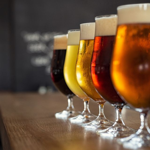 Four glasses of beer of varying types lined up on a bar.