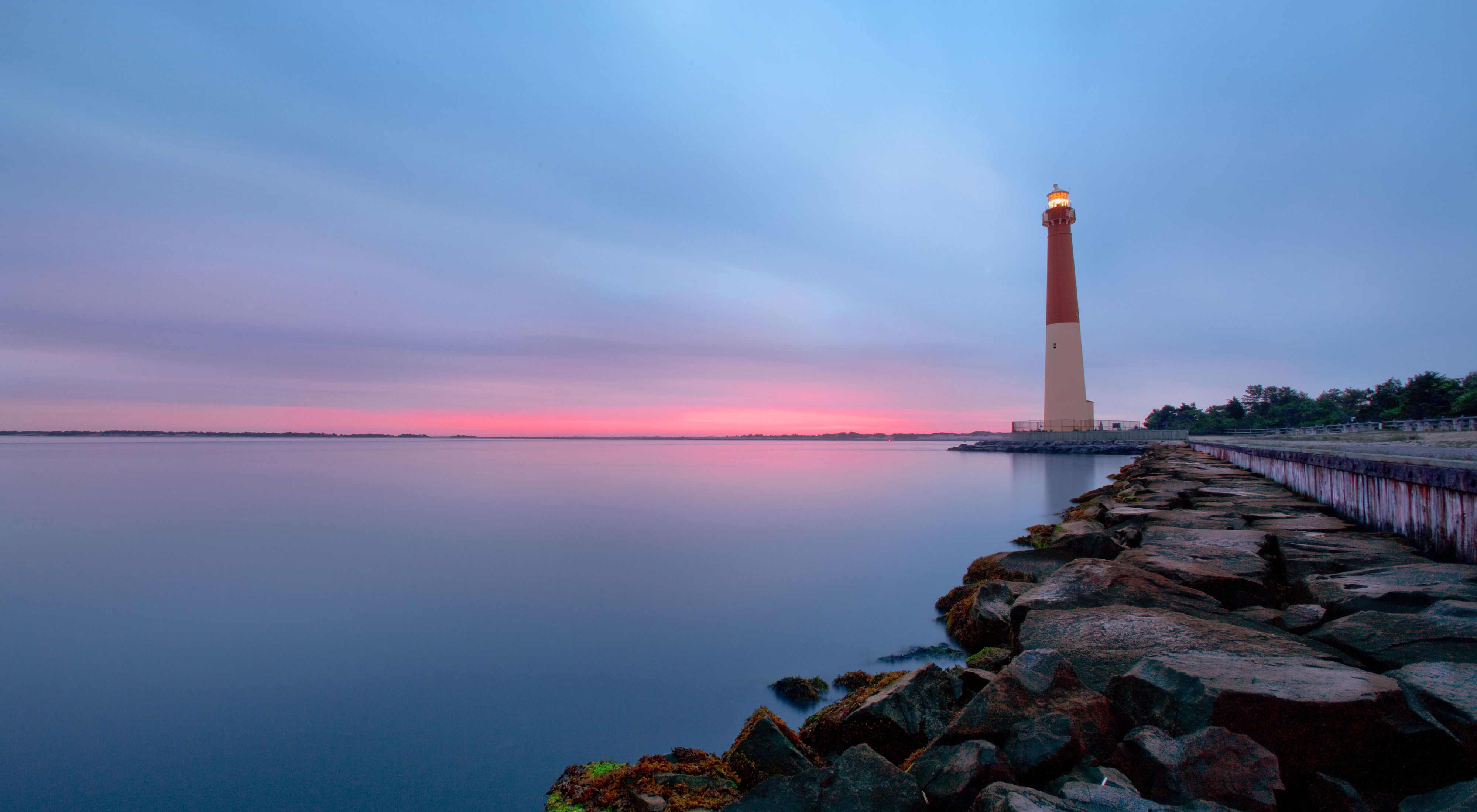 Sun setting over a lighthouse, with pink and blue sky.