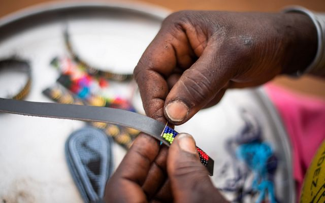 Joyce Lelukai crafts a beaded strap for Beadworks at her home (boma) in Kalama Conservancy.