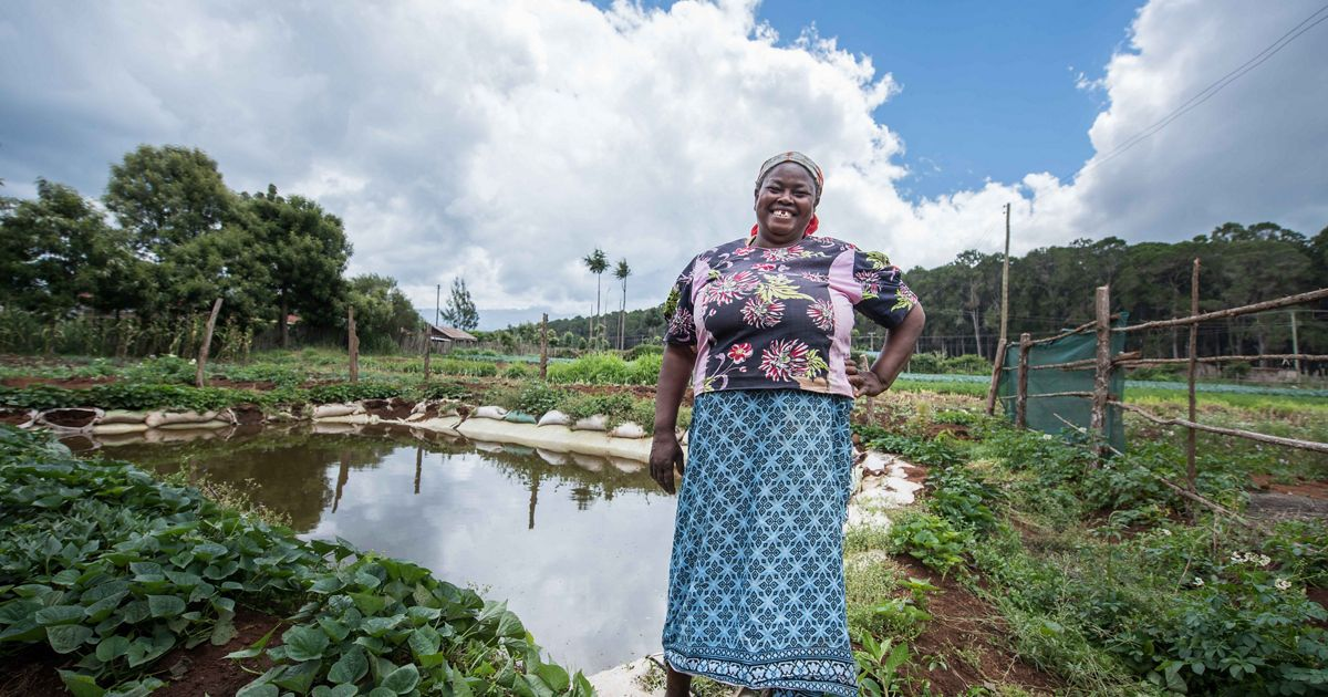 Elena stands in front of the water pan she received from the Tana-Nairobi Water Fund.