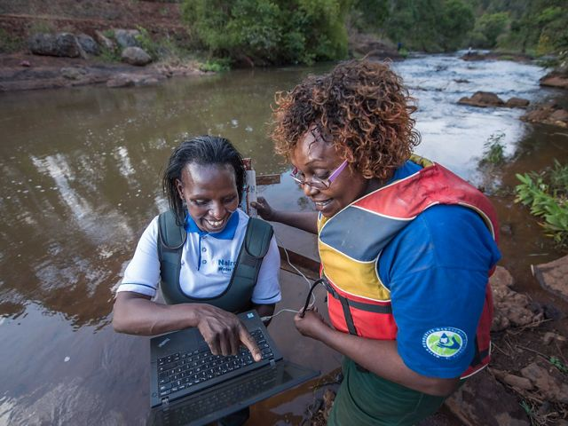 Faith Mbathi (left) and Jane Njoroge (right) of Kenya's Water Resources Authority use technology to measure water flows as part of the Water Fund.