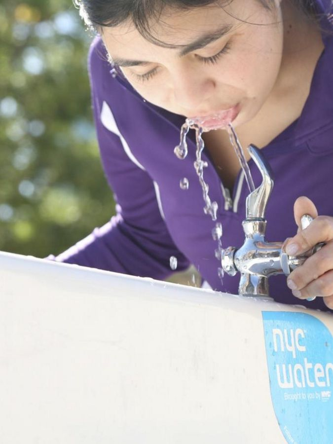 Close up of person drinking from a water fountain.