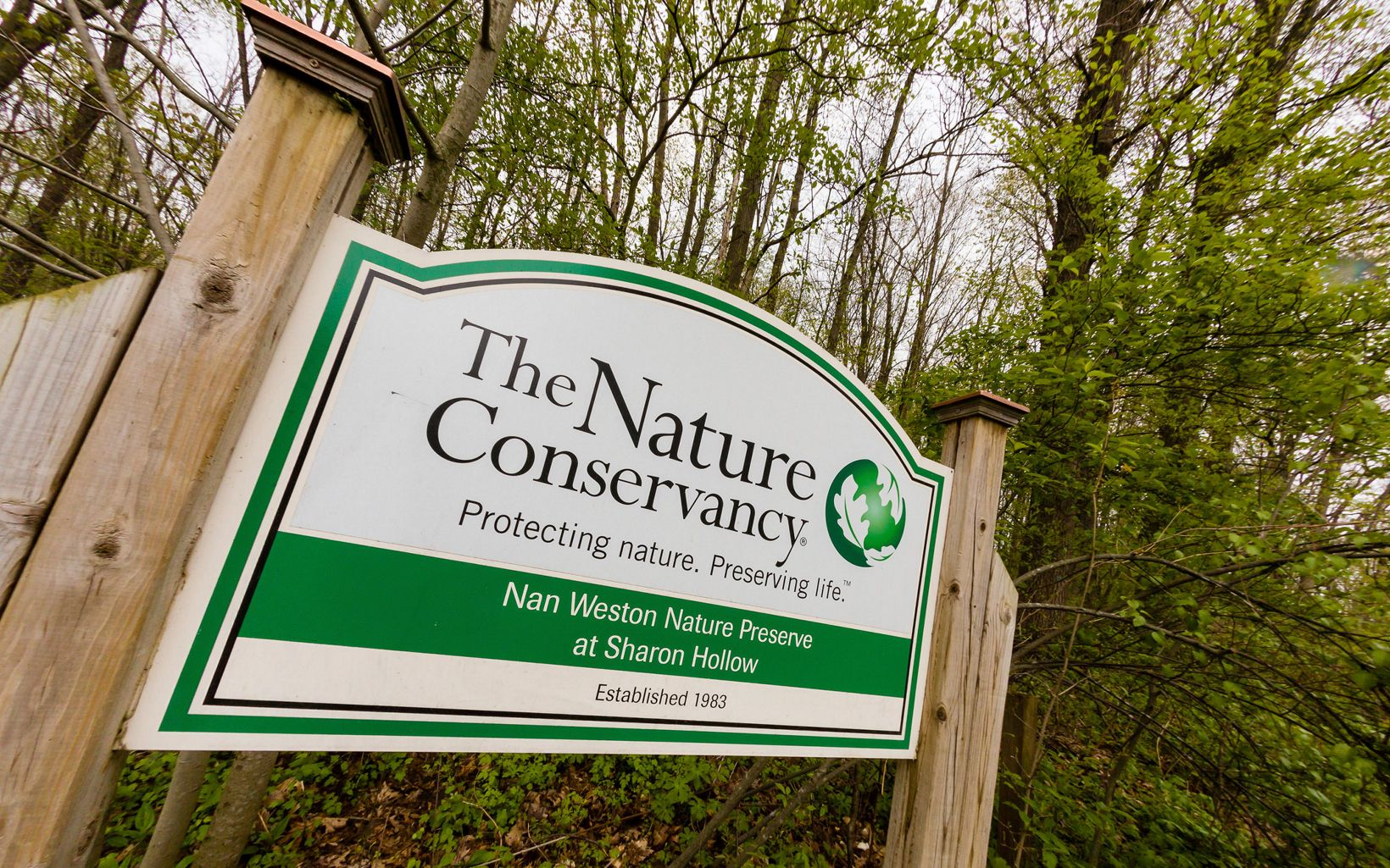 Sign with the TNC logo, reading 'Nan Weston Preserve at Sharon Hollow.'