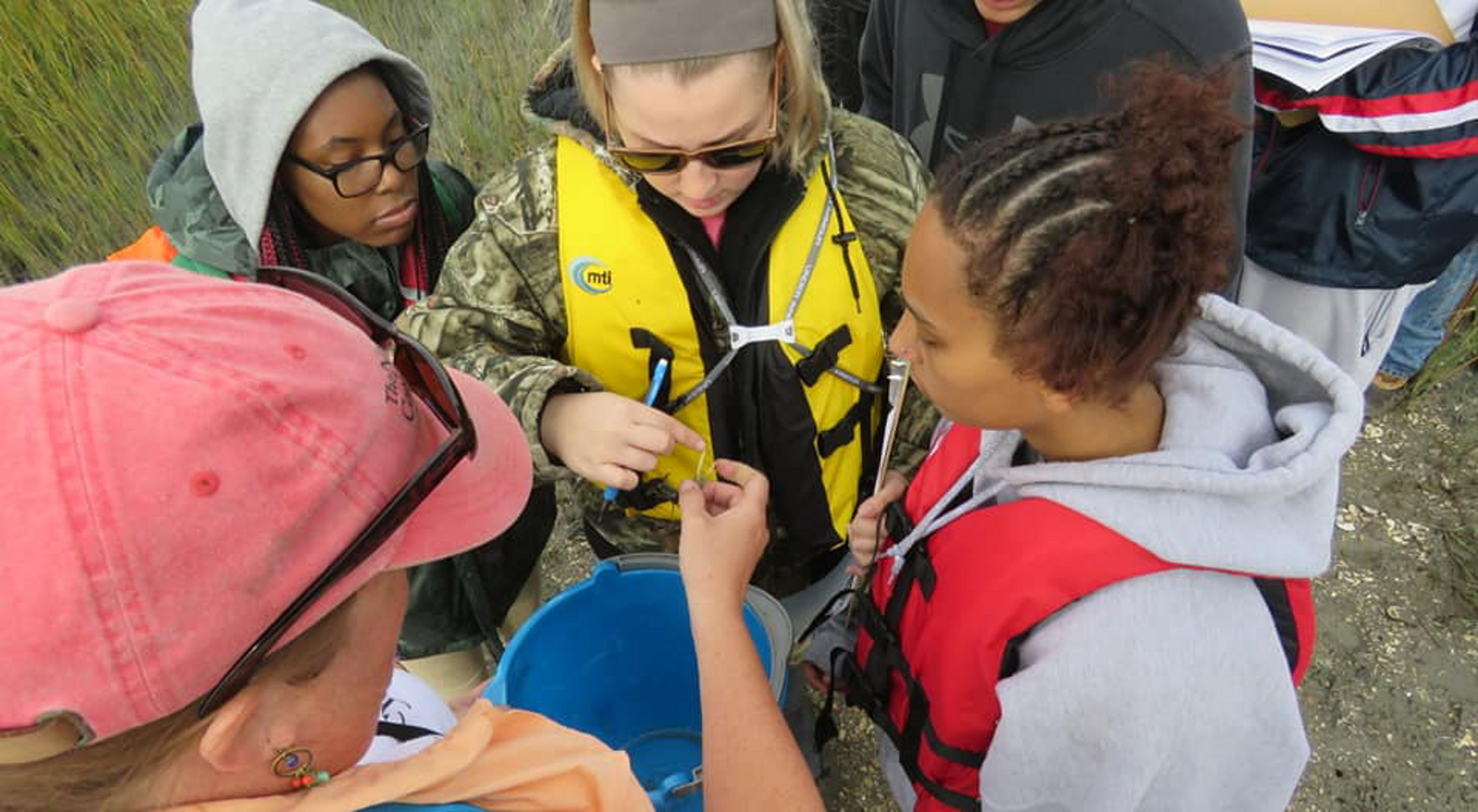 View looking down on four students crowding around a TNC staff member who is holding out a small fiddler crab for them to see.