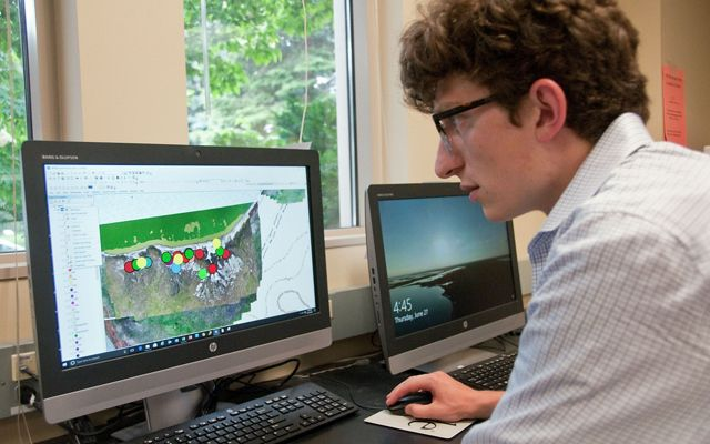 Student researcher stitches together map data collected by drone.