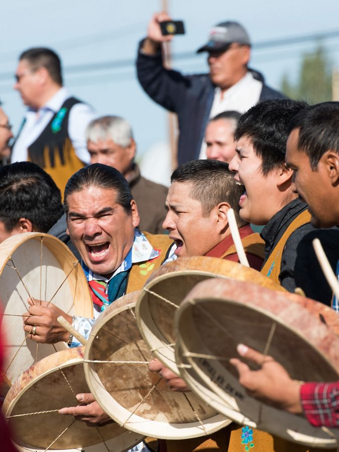 A group of eight men are yelling and beating drums