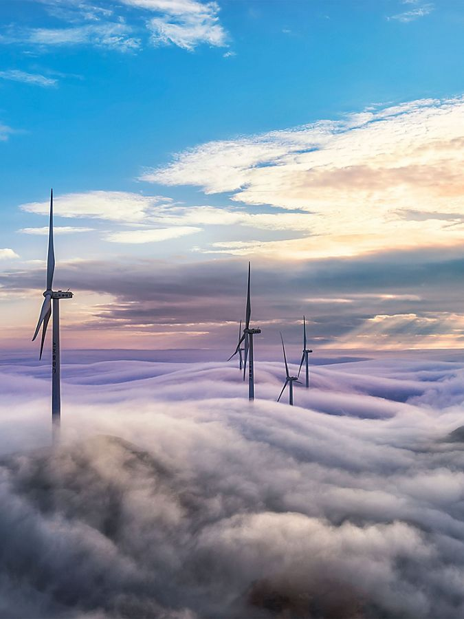 wind turbines poking up above low hanging clouds