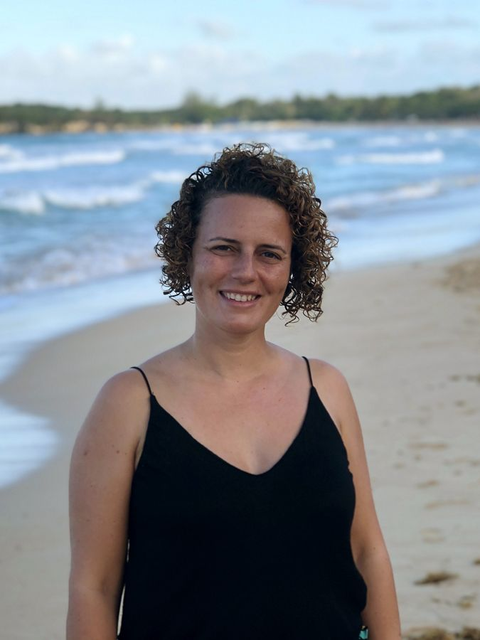 a portrait of a smiling woman on a beach