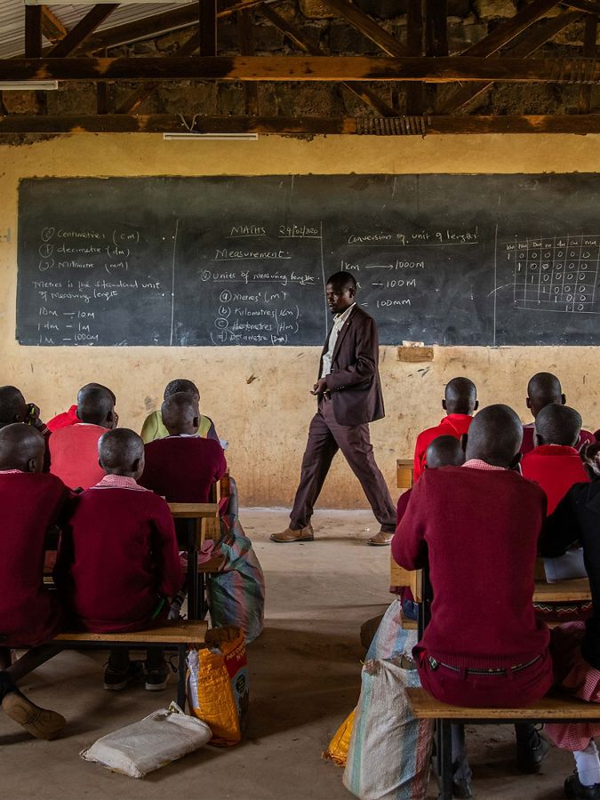 a man stands at the front of a classroom of children