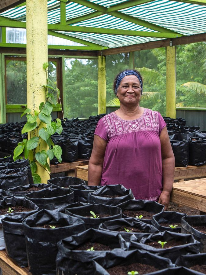 a smiling woman stands in plant nursery
