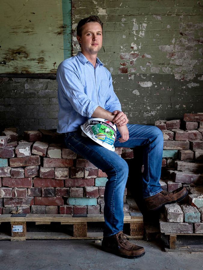 man holds a hardhat, sits on a pile of reclaimed bricks