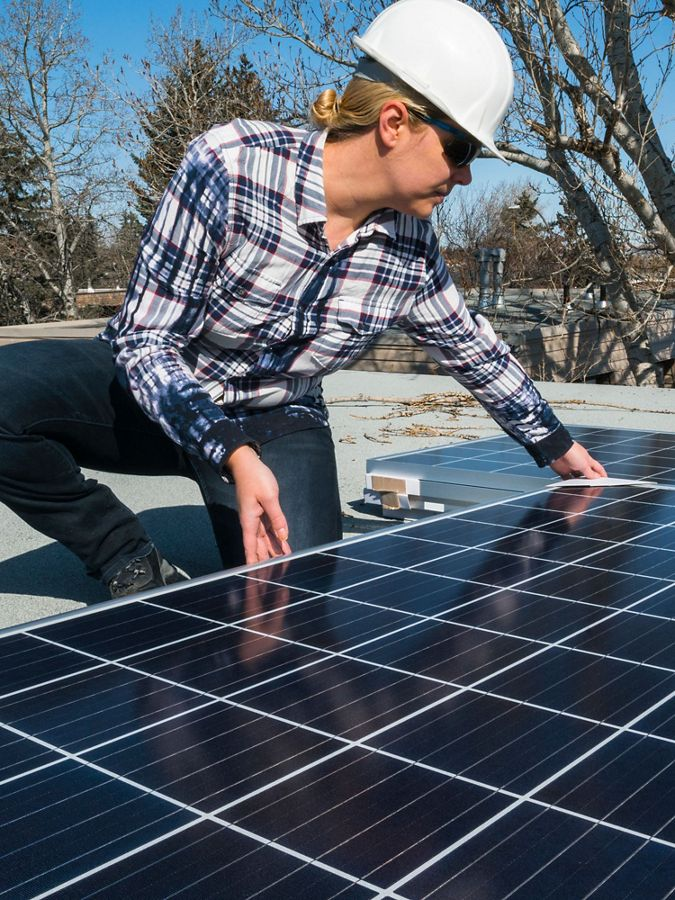woman installs solar panel on a roof