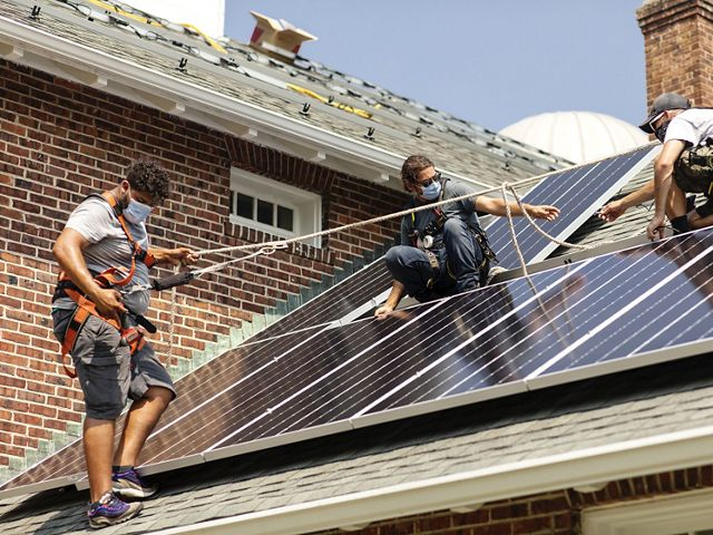 Three workers wearing masks up on a roof installing solar panels. Hilario Minaya is on the left, standing on the roof with a harness and rope for safety.