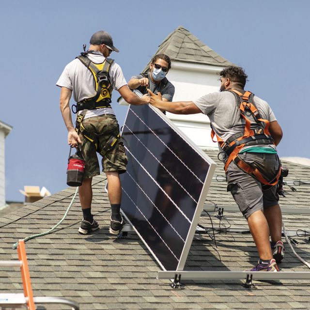 Three masked workers, viewed at center, on top of a roof installing a solar panel.