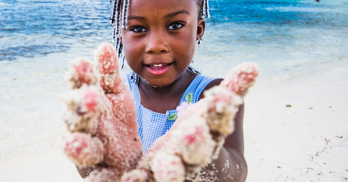 A young girl plays on a beach in The Bahamas.