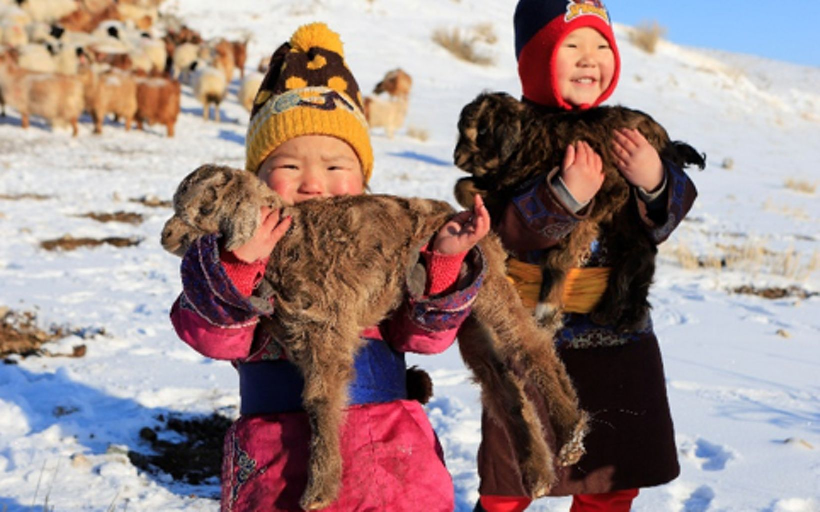 Two young Mongolian children stand in the snow while each holding a baby goat.
