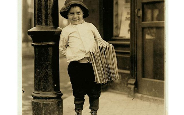A young boy wearing a floppy hat smiles while holding a