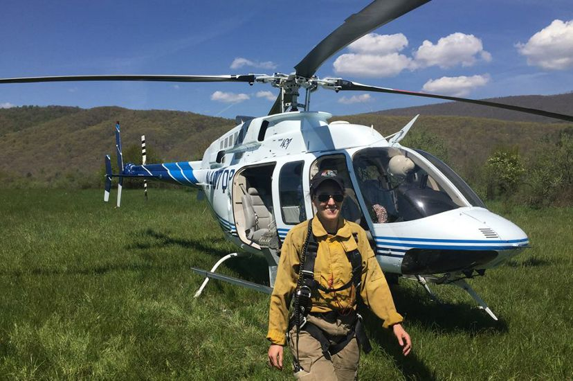 A woman wearing yellow fire retardant gear stands in front of a white helicopter. The helicopter sits in an open meadow with a line of mountain ridges behind it.