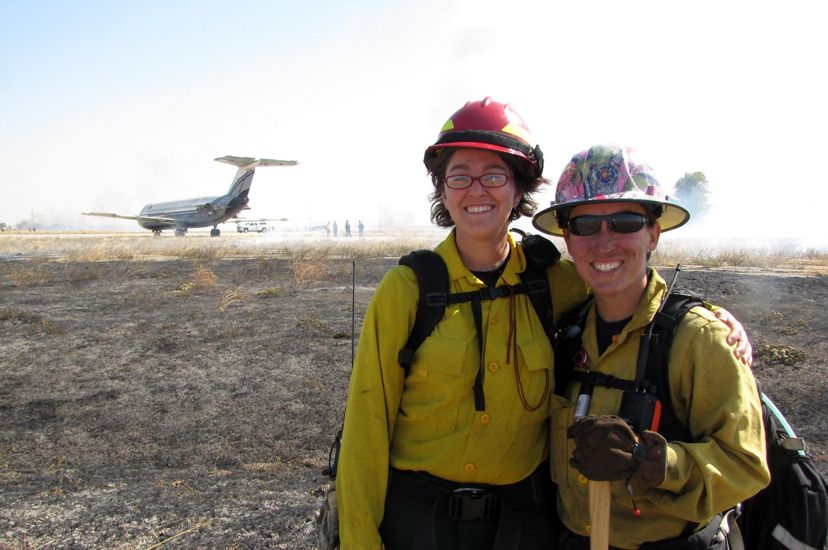 Two women pose together at a controlled burn. The ground around them has recently been burned. They are both wearing hard hats and yellow fire retardant gear.
