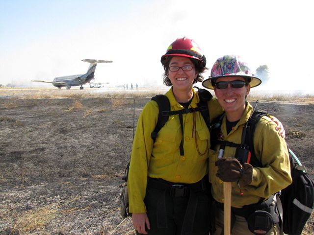 Two women pose together during a controlled burn. Their smiling faces are streaked with soot.