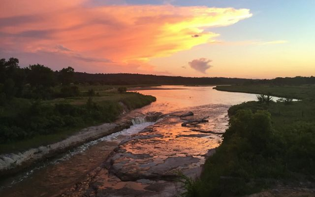 The sun rises over the winding river at the Niobrara Valley Preserve, the largest tract of intact grasslands, which offers climate resiliency.