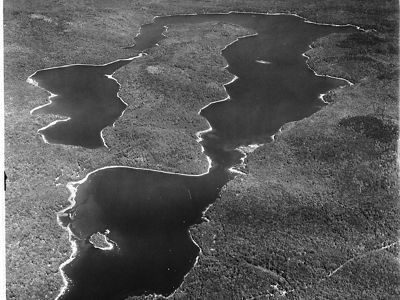 An aerial view of of a wooded peninsula between two lakes.