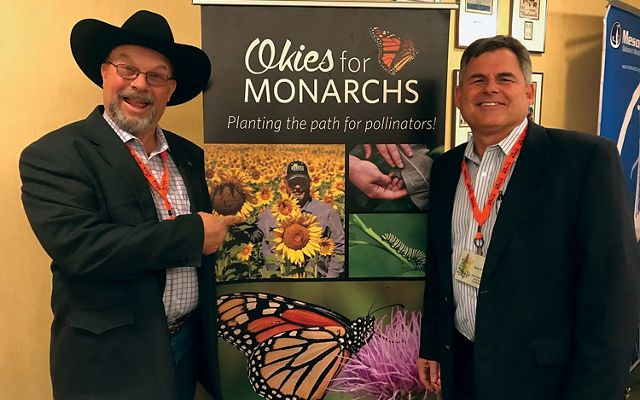 "Two men standing in front of a banner with text that reads ""Okies For Monarchs."""