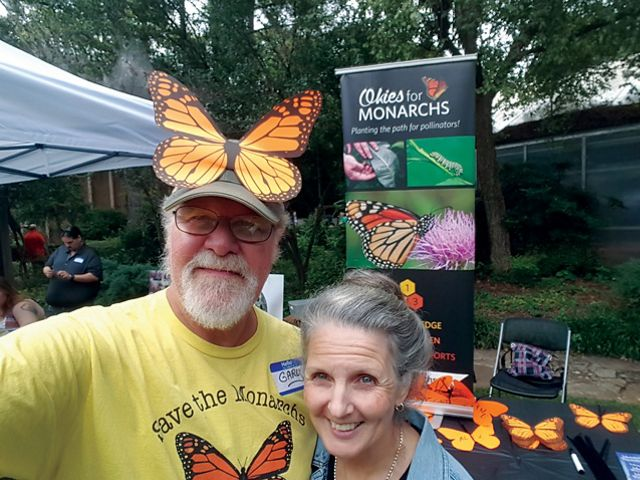 Two people standing together with monarch butterflies.