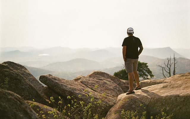 Man standing on mountain rocks overlooking the valley.