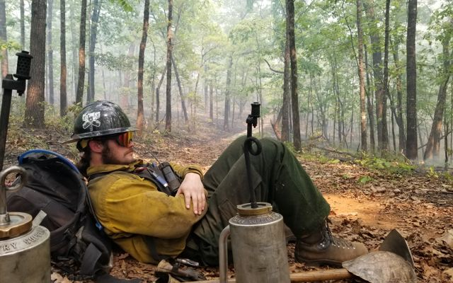 Man sits under a tree next to a drip torch during a controlled burn.