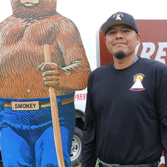 Man standing next to Smokey Bear.