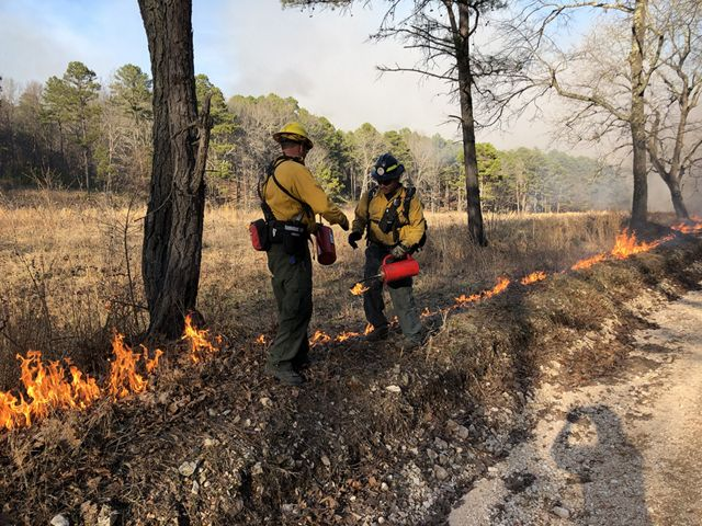 Two men exchanging equipment during a controlled burn.