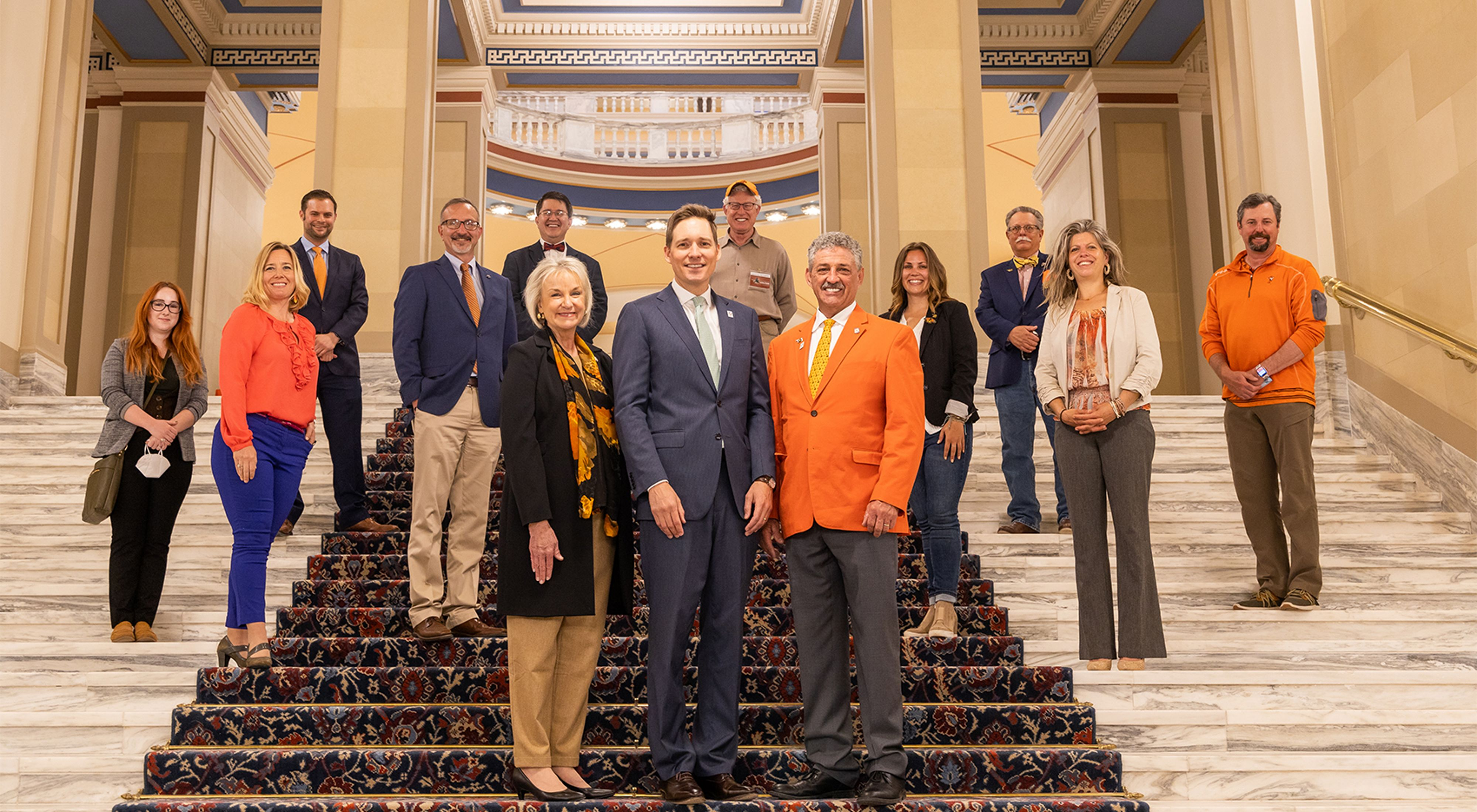 A group of about 15 people, with social distancing, many wearing orange, standing and posing for the camera on marble steps at the state capitol.