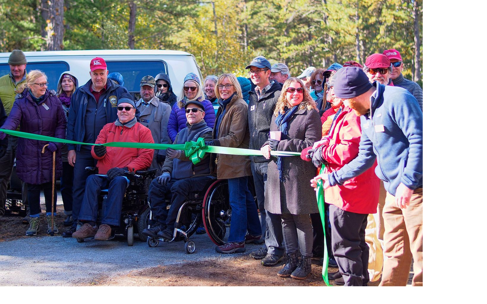 U.S. Senator Maggie Hassan and NH State Director Mark Zankel help in cutting the ribbon to open a new accessible trail at the Ossipee Pine Barrens Preserve.