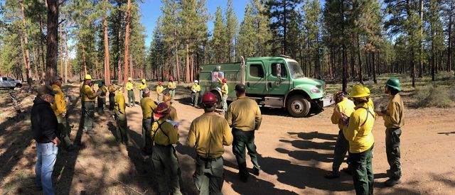 Photo of a multi-agency team standing in circle, preparing for a controlled burn in Oregon.