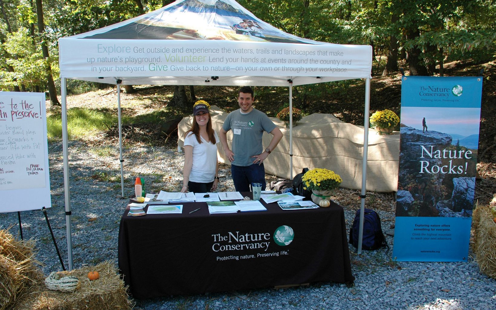 Two TNC staff members stand under a tent.