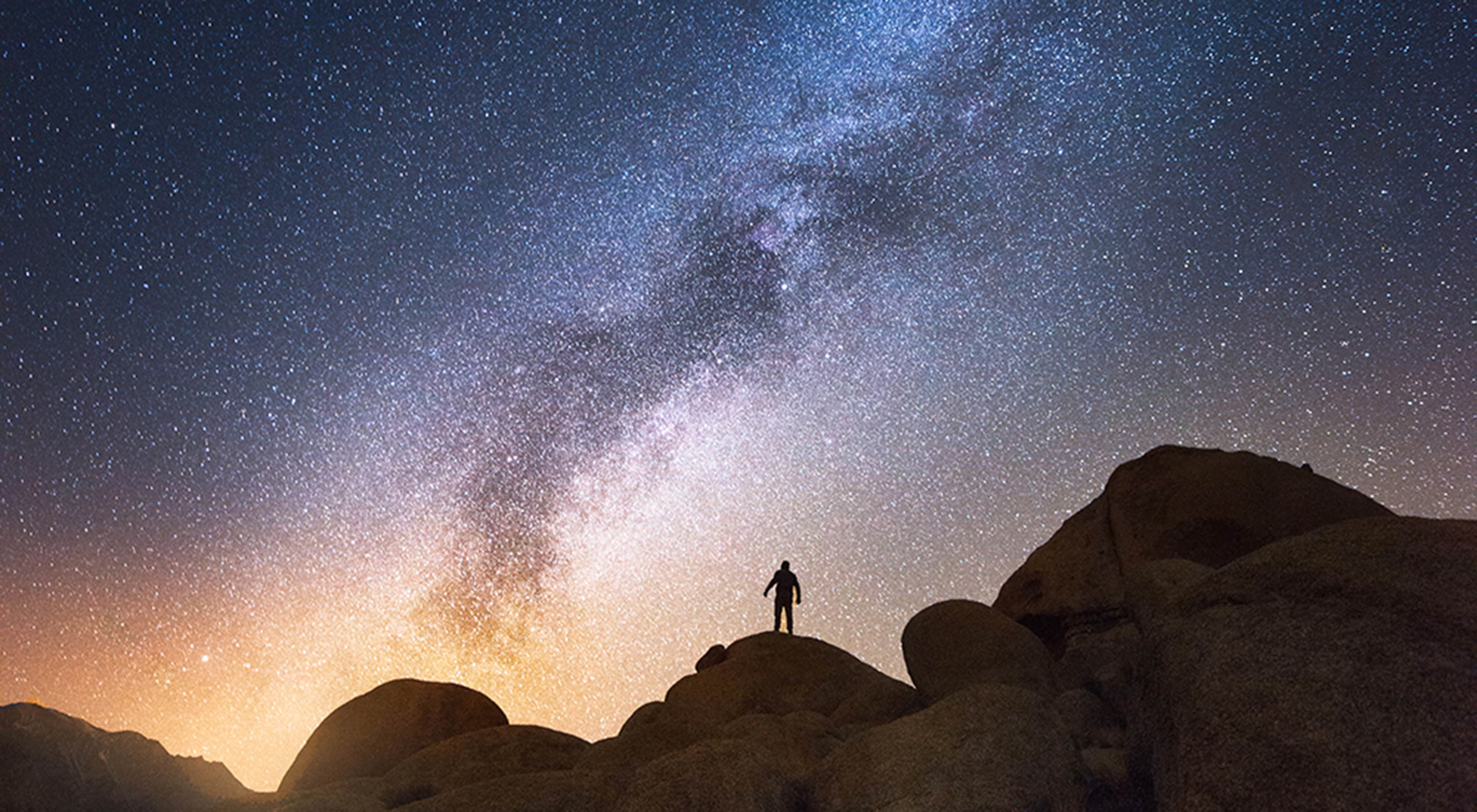 A hiker stands on a hill on a starry night.