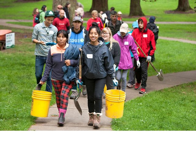 A group of smiling volunteers at Mount Tabor Park in Portland, Oregon.