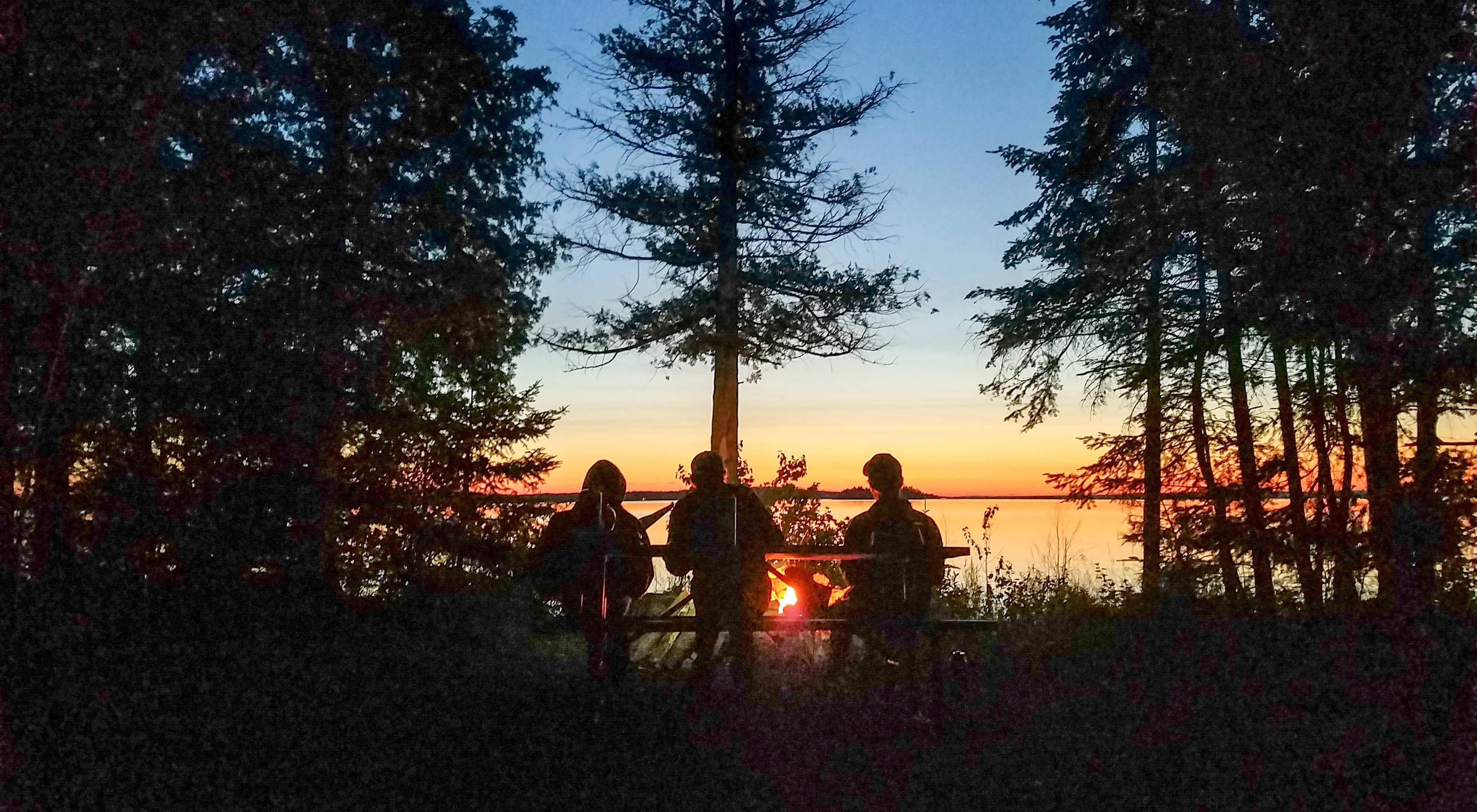Three silhoutted people sitting around a campfire in a forest at sunset.