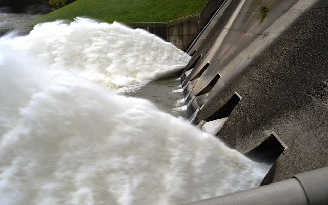 White water rushes away from openings in a concrete dam.