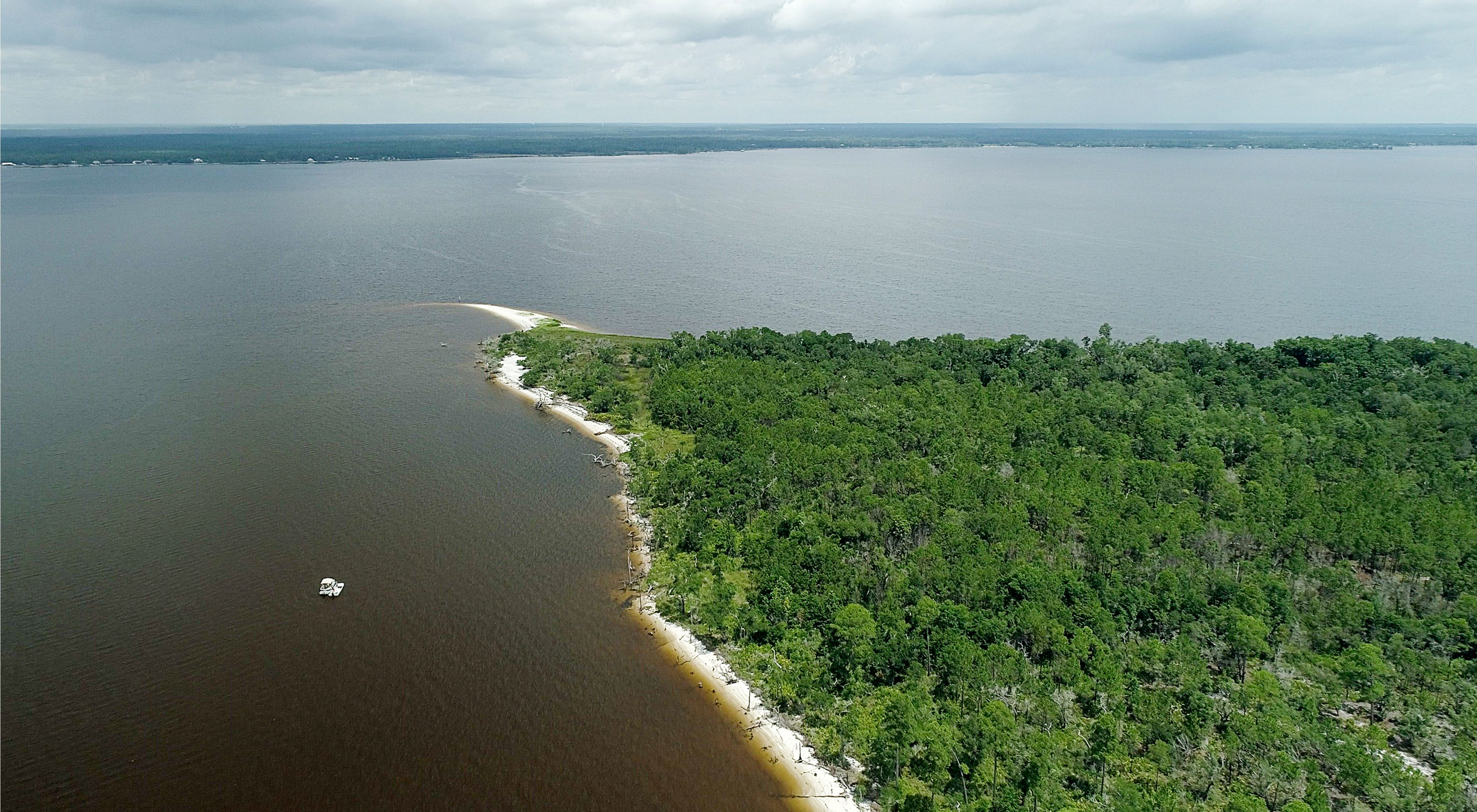 A tree-covered point of land with a sand spit at the end, extending into Pensacola Bay in Santa Rosa County, Florida.