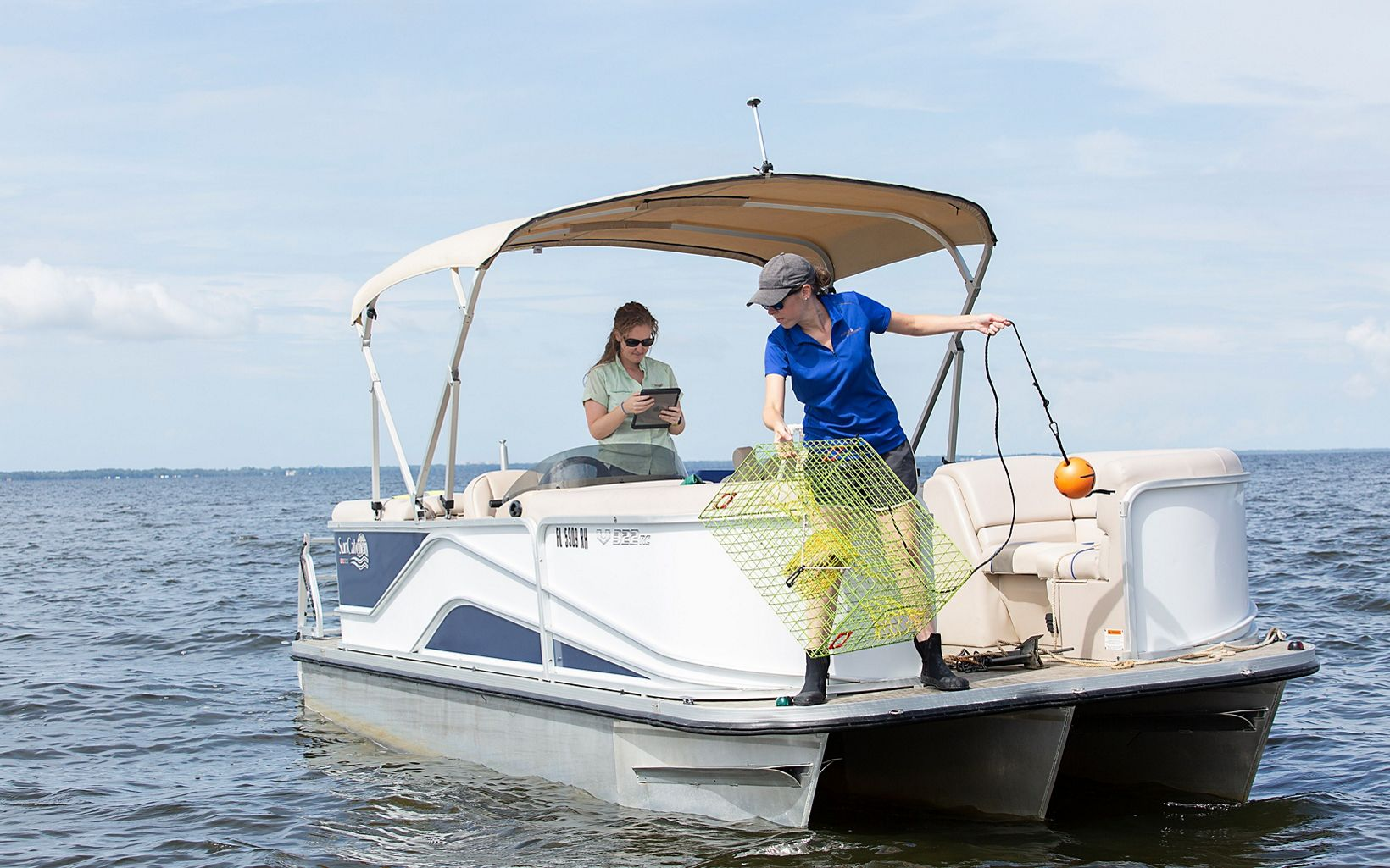 Scientists conducting oyster reef restoration monitoring travel in a boat on Pensacola Bay.