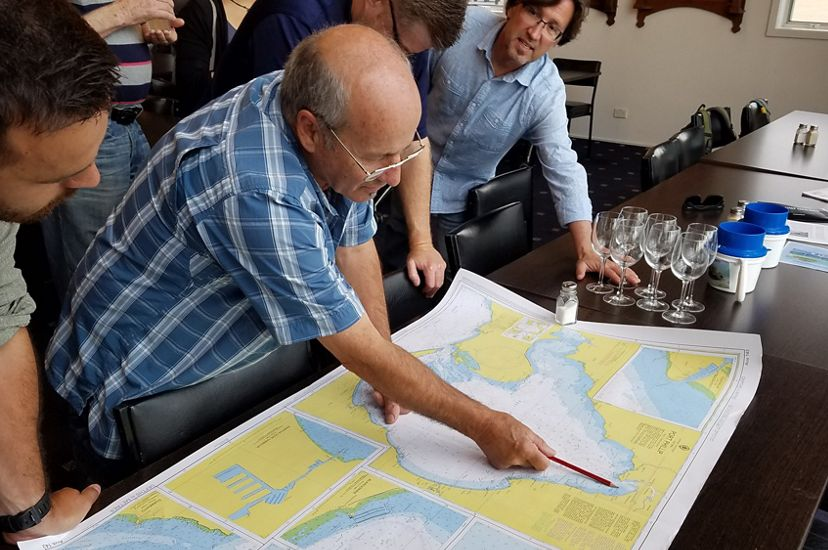 A group of five men crowd around a long table looking at a large map. One man uses a pencil to point to a place on the map.