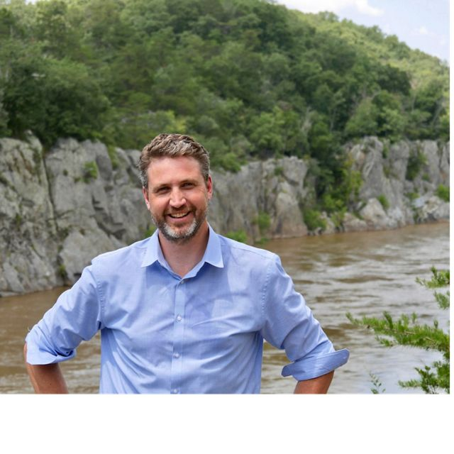 A smiling man stands in front of a river.