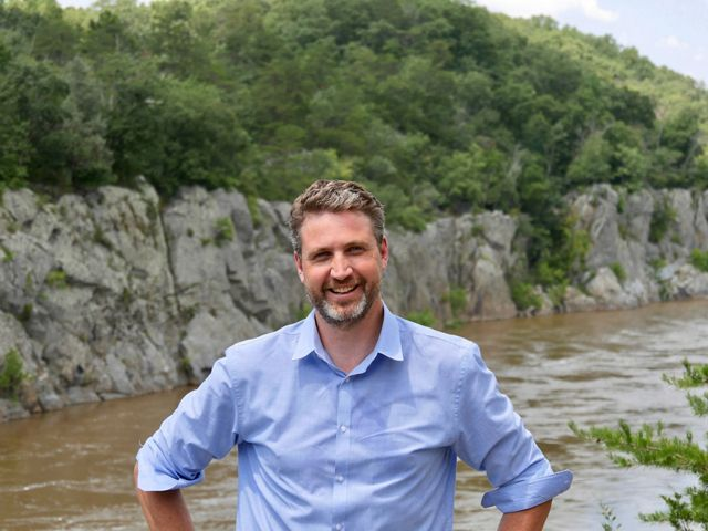 A smiling man wearing a blue shirt stands in front of the Potomac Gorge. The Potomac River rushes past below him.